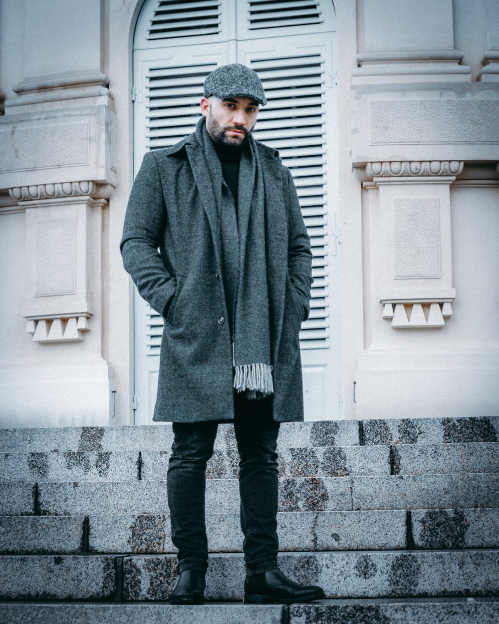 man in gray coat standing on gray concrete floor during daytime