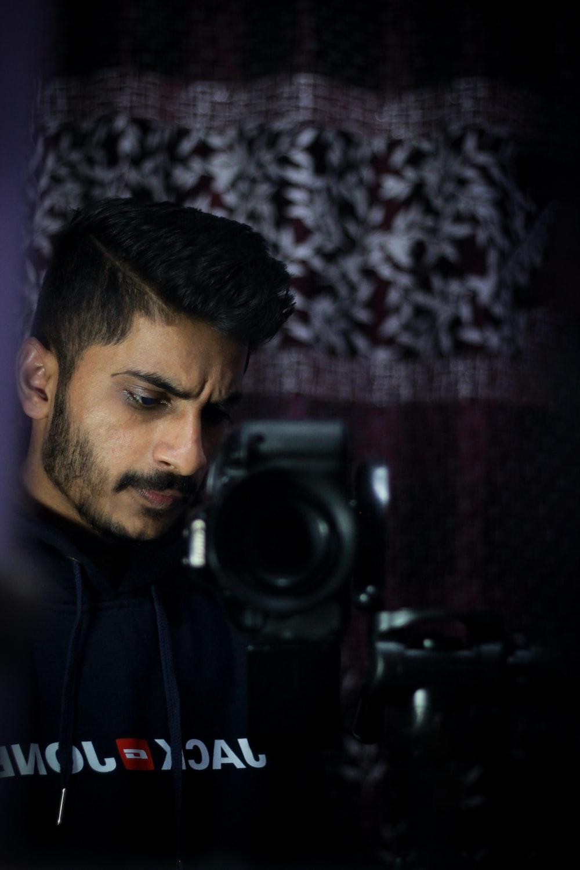 man in black hoodie standing near black camera