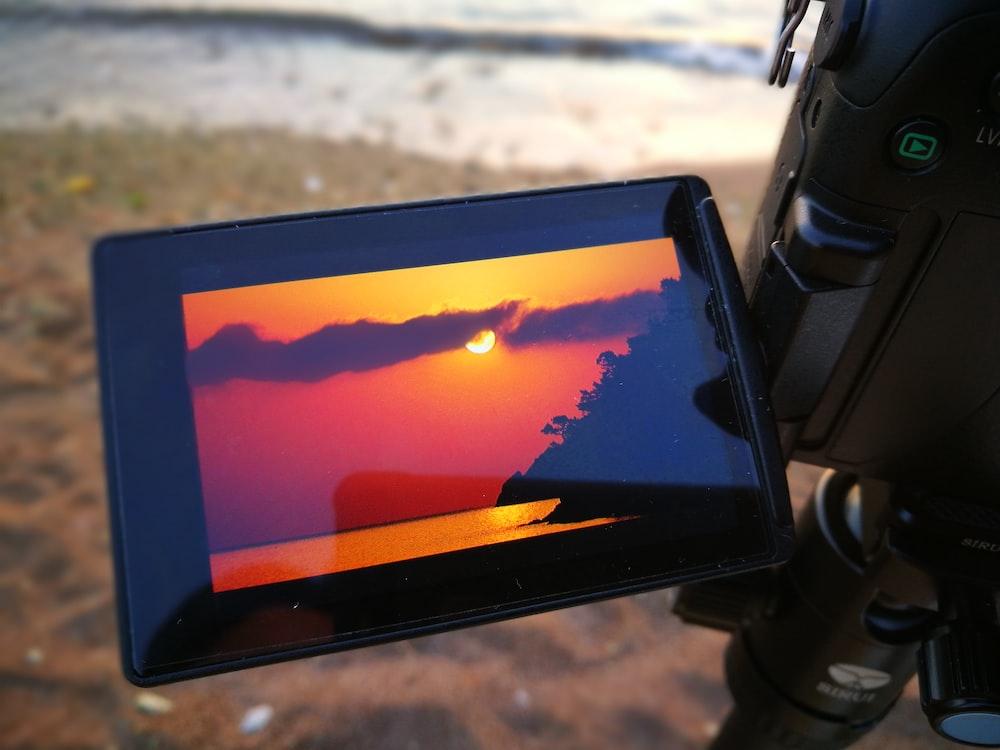 black tablet computer turned on displaying orange and blue sky