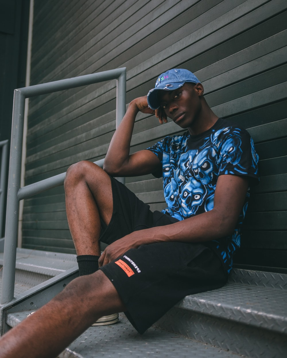 man in blue and white floral shirt and black shorts sitting on gray wooden stairs
