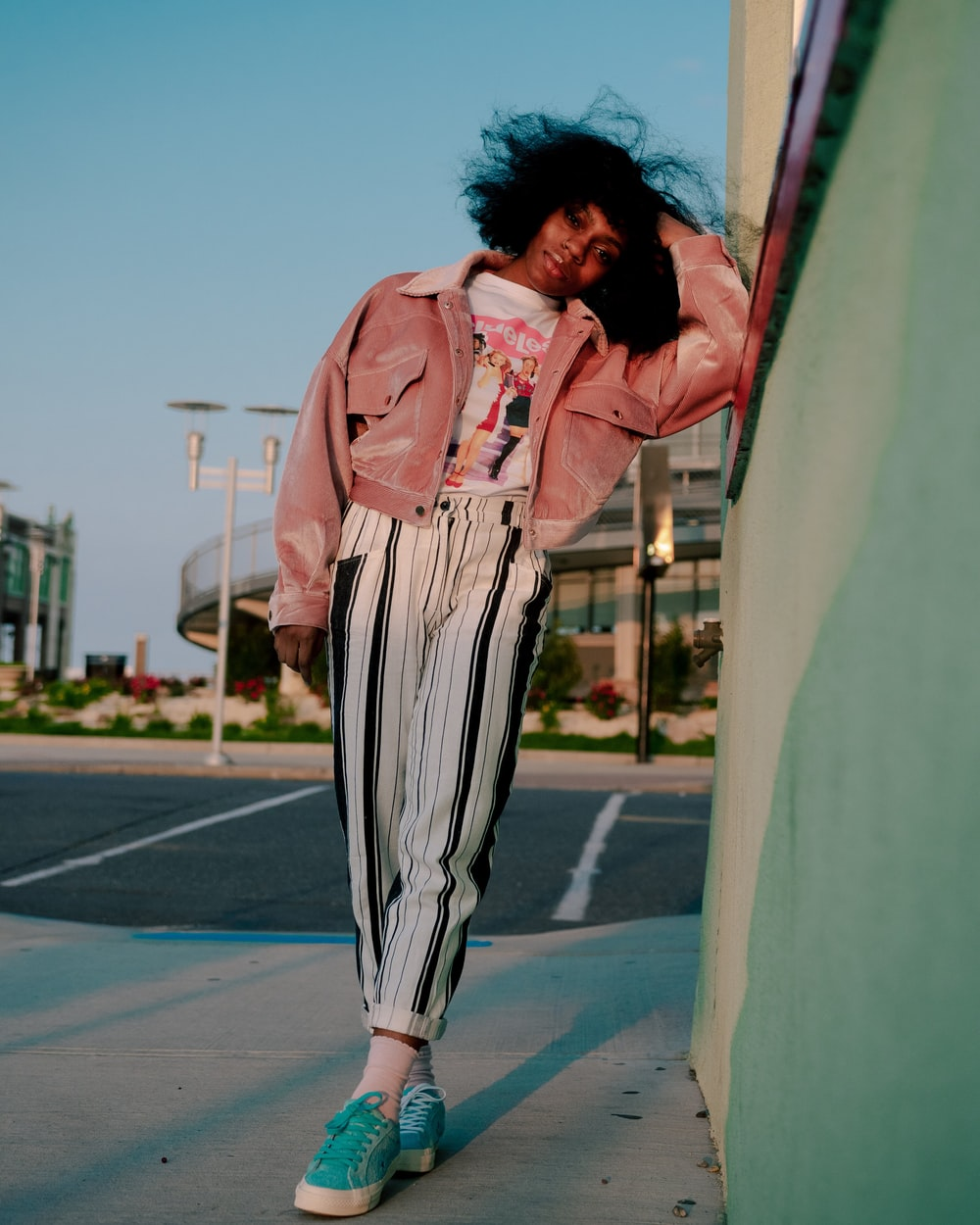 woman in pink jacket and black and white striped pants standing on gray concrete floor during