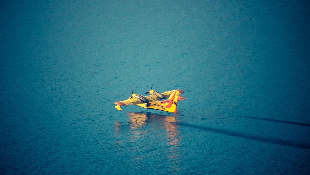 2 people riding on yellow kayak on blue sea during daytime
