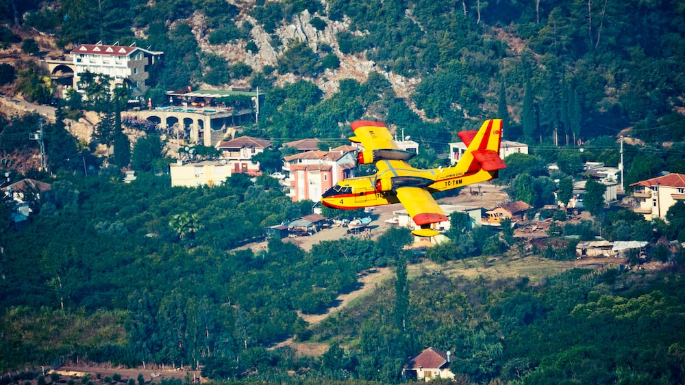 yellow and red plane flying over green grass field during daytime