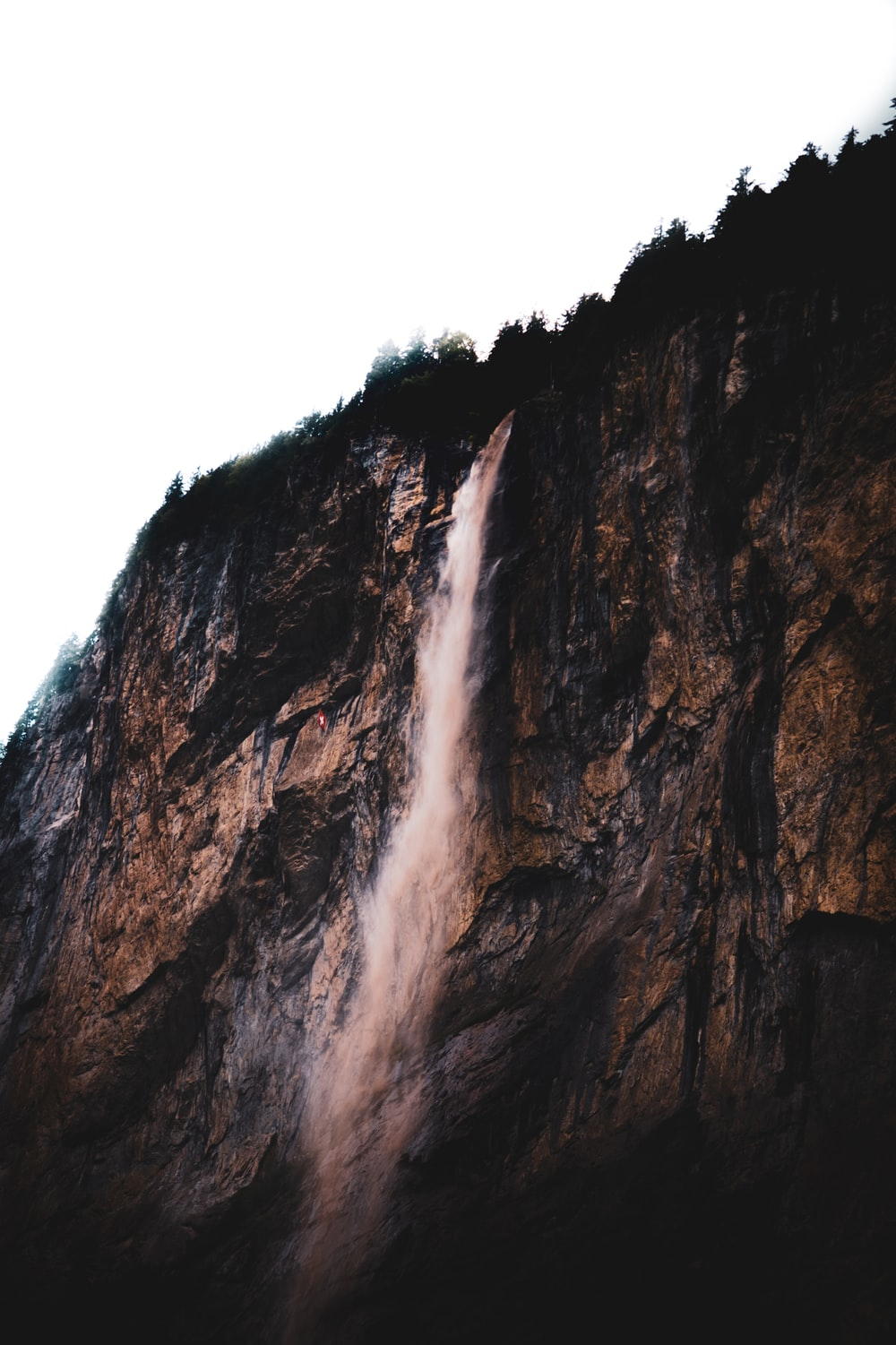 brown rocky mountain with waterfalls