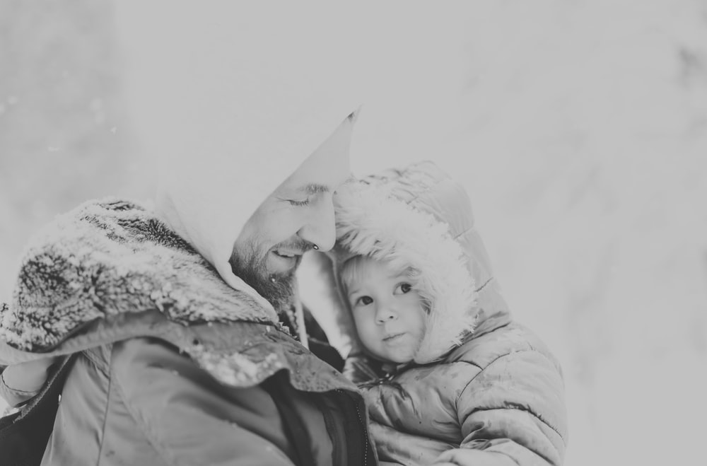grayscale photo of baby in white knit cap and jacket