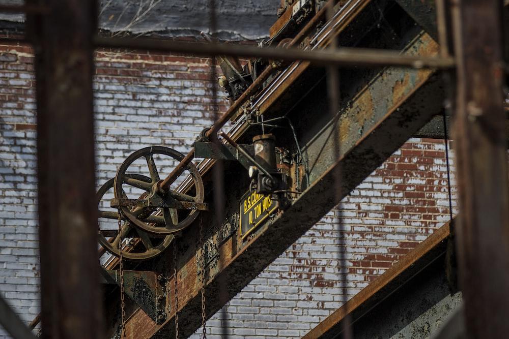 brown metal wheel on brown brick wall