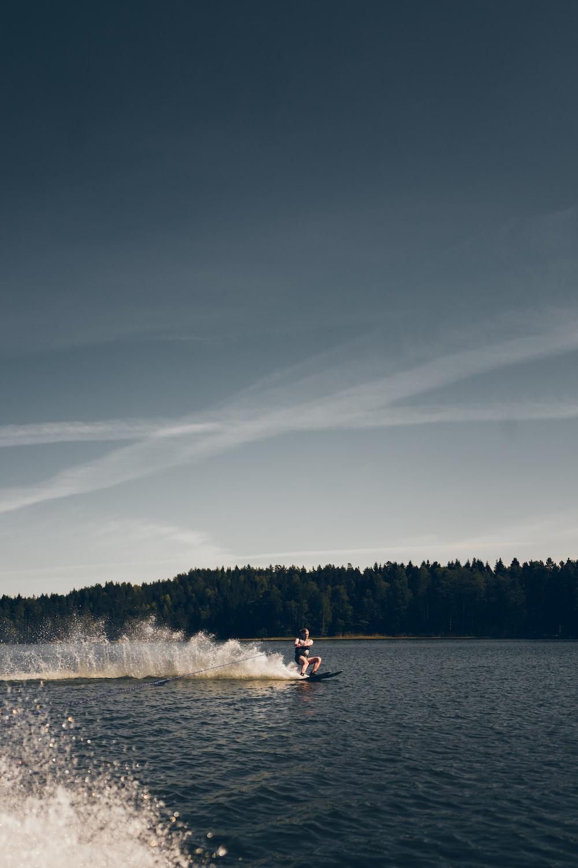 2 people riding on white kayak on lake during daytime