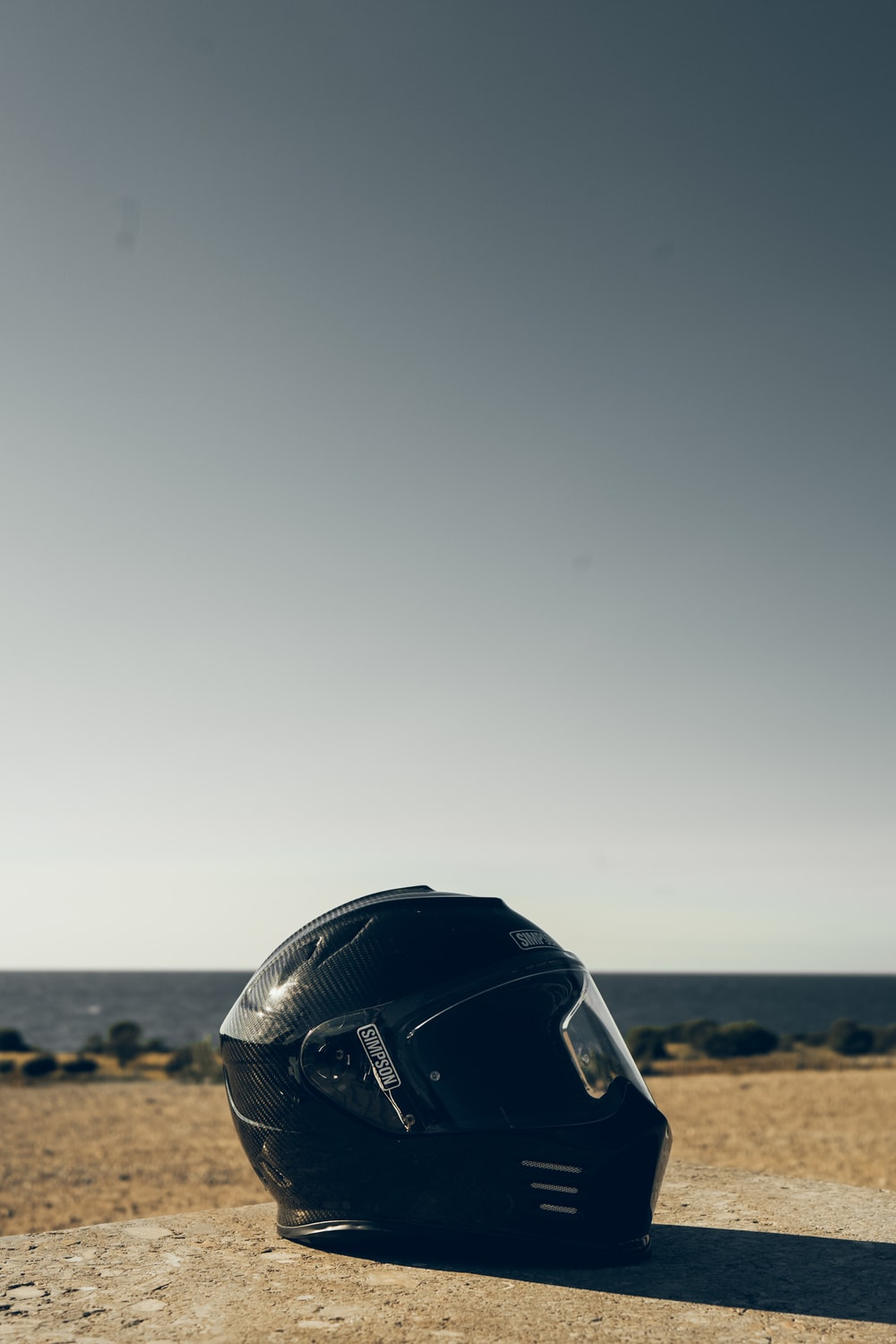 black motorcycle helmet on brown sand during daytime