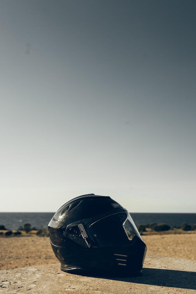black motorcycle helmet on brown sand during daytime