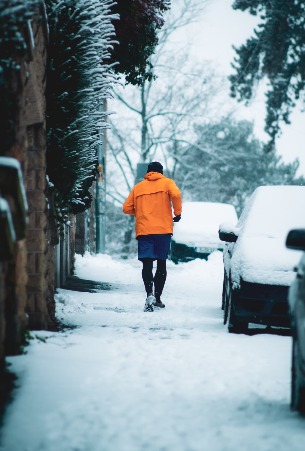 person in orange hoodie walking on snow covered pathway during daytime