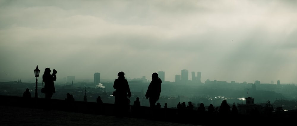 silhouette of people standing on the ground during daytime