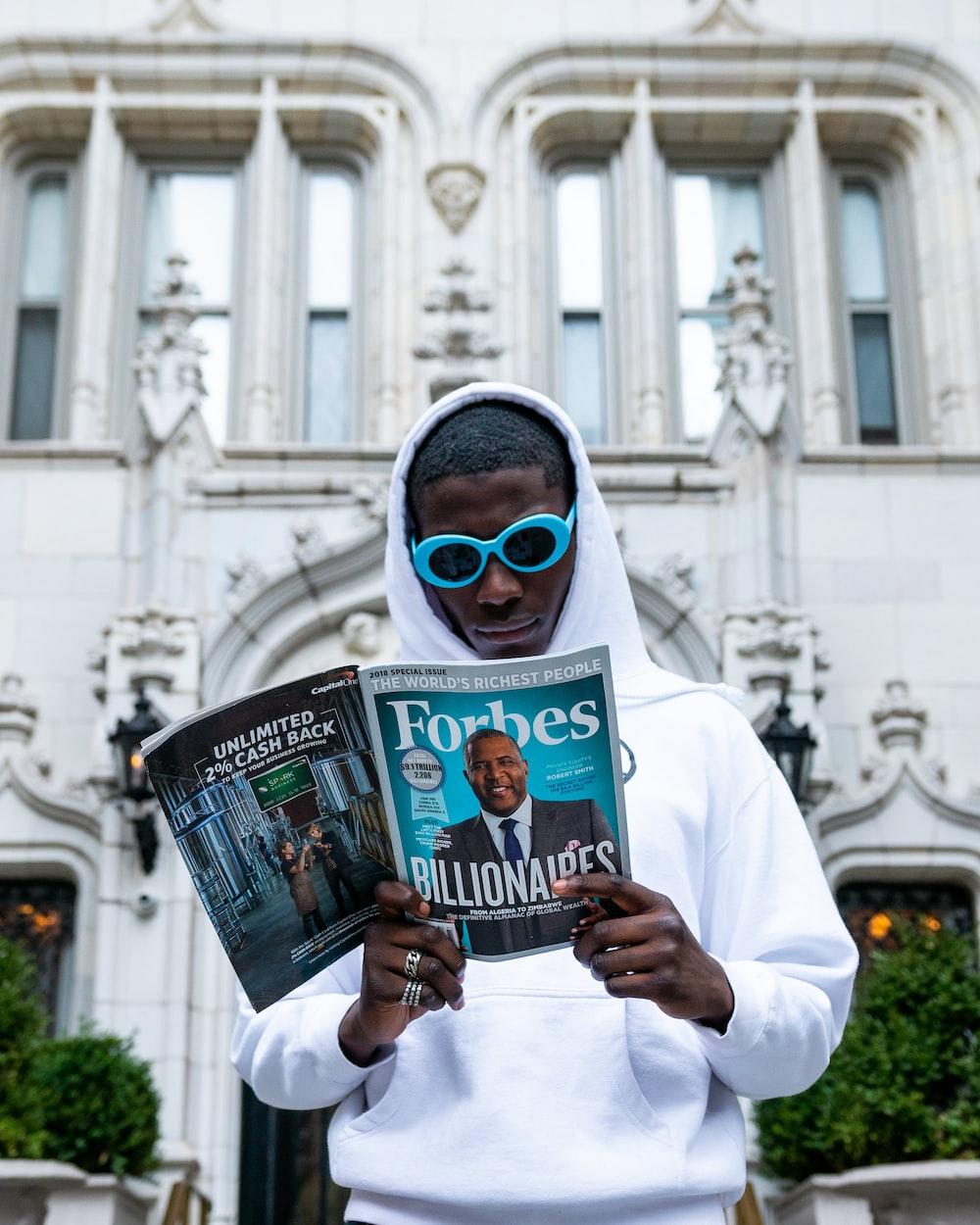 man in white thobe holding newspaper