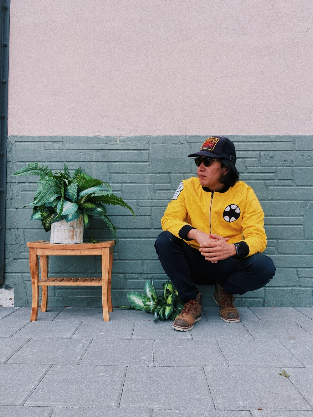 man in yellow crew neck t-shirt and black pants sitting on brown wooden chair