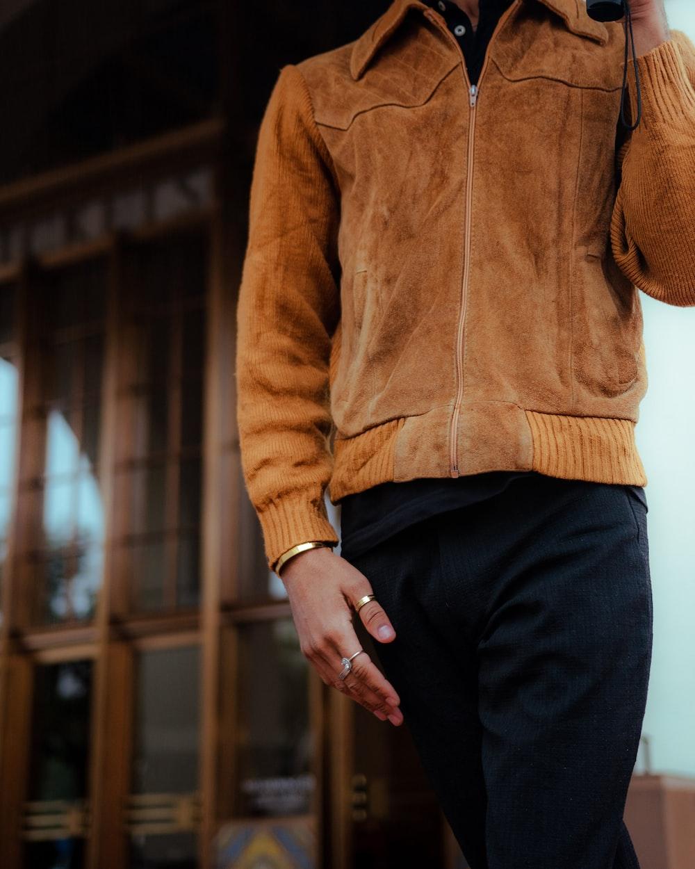 man in brown zip up jacket and black pants