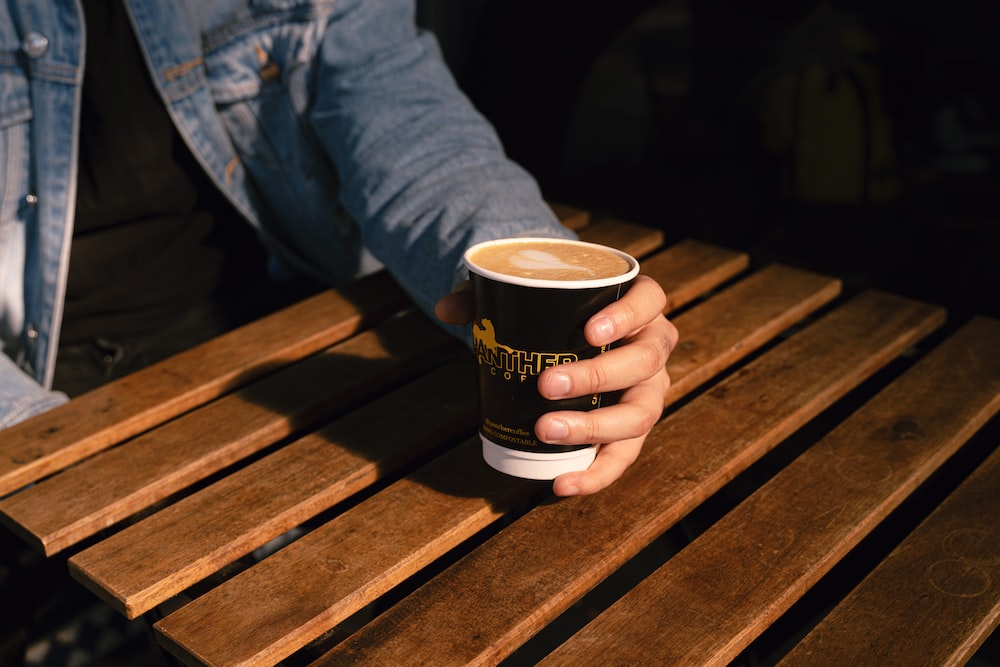 person holding black and white disposable cup