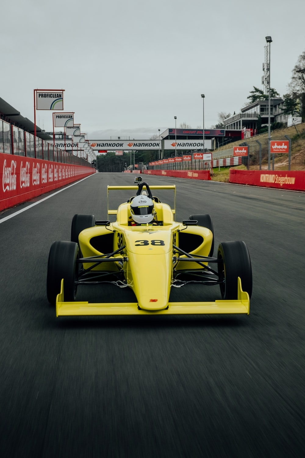 yellow and black f 1 car on road during daytime