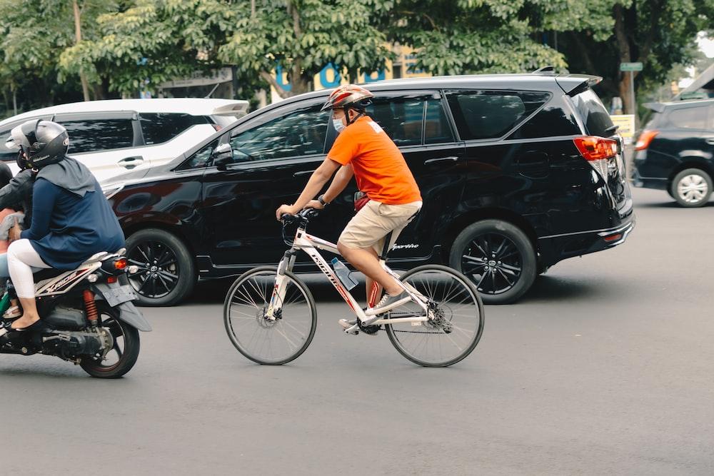 man in orange t-shirt riding on white bicycle