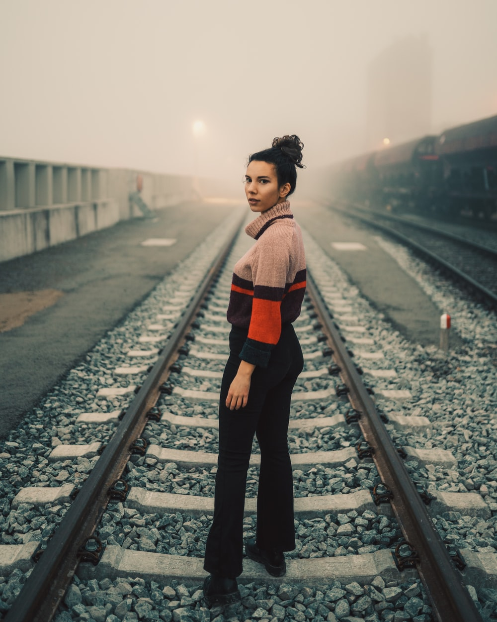 woman in red and black long sleeve shirt and black pants standing on train rail during