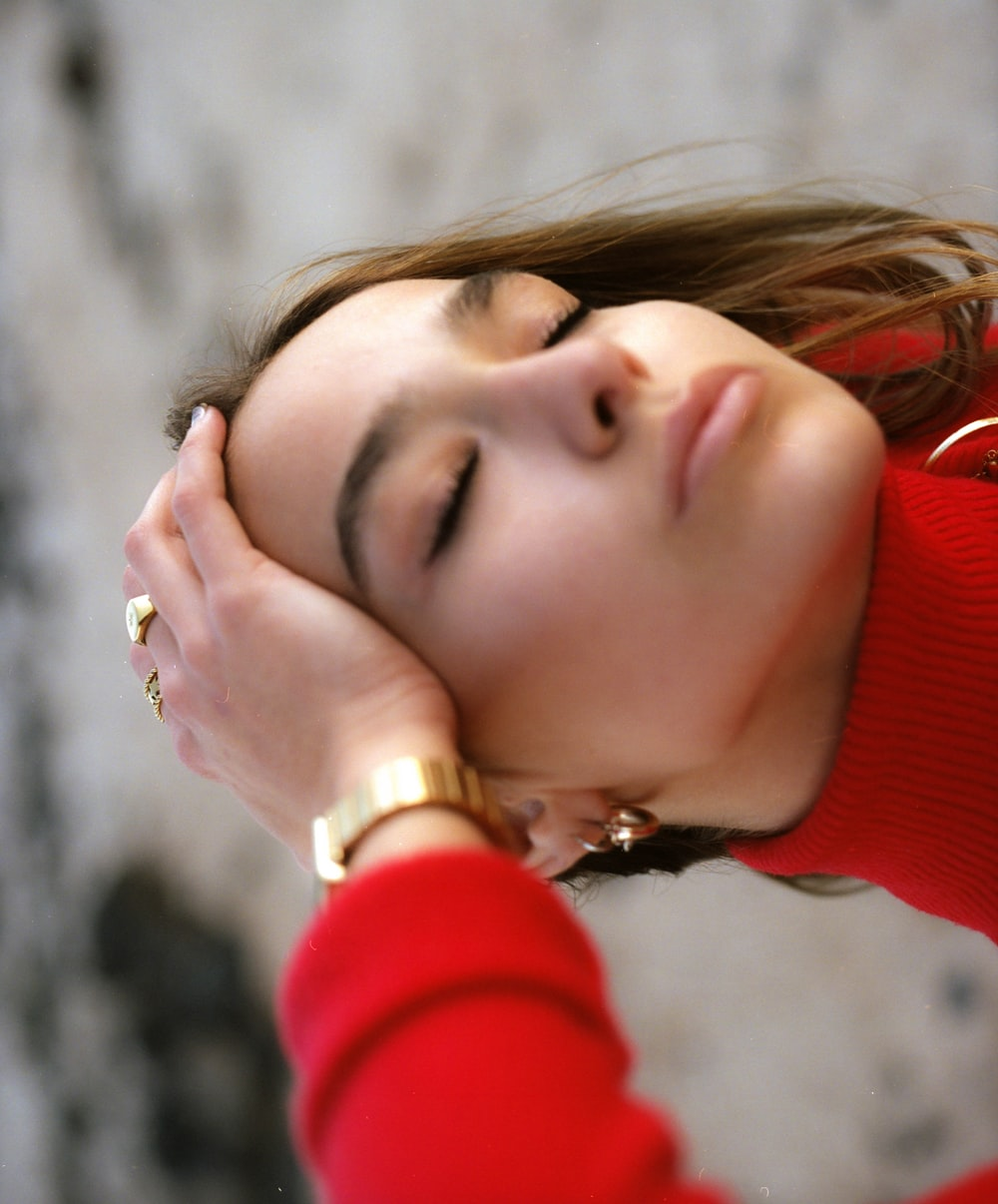 woman in red sweater holding her face