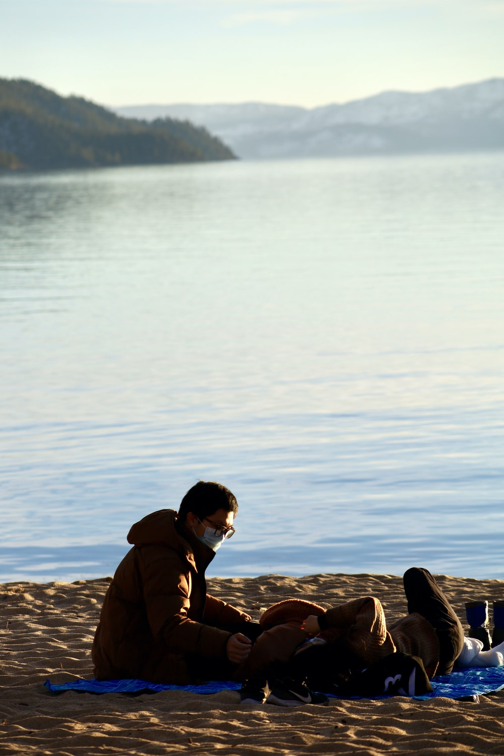 man in brown jacket sitting on rock near body of water during daytime