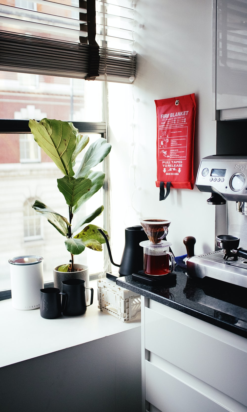 red and silver coffee maker beside white ceramic mug