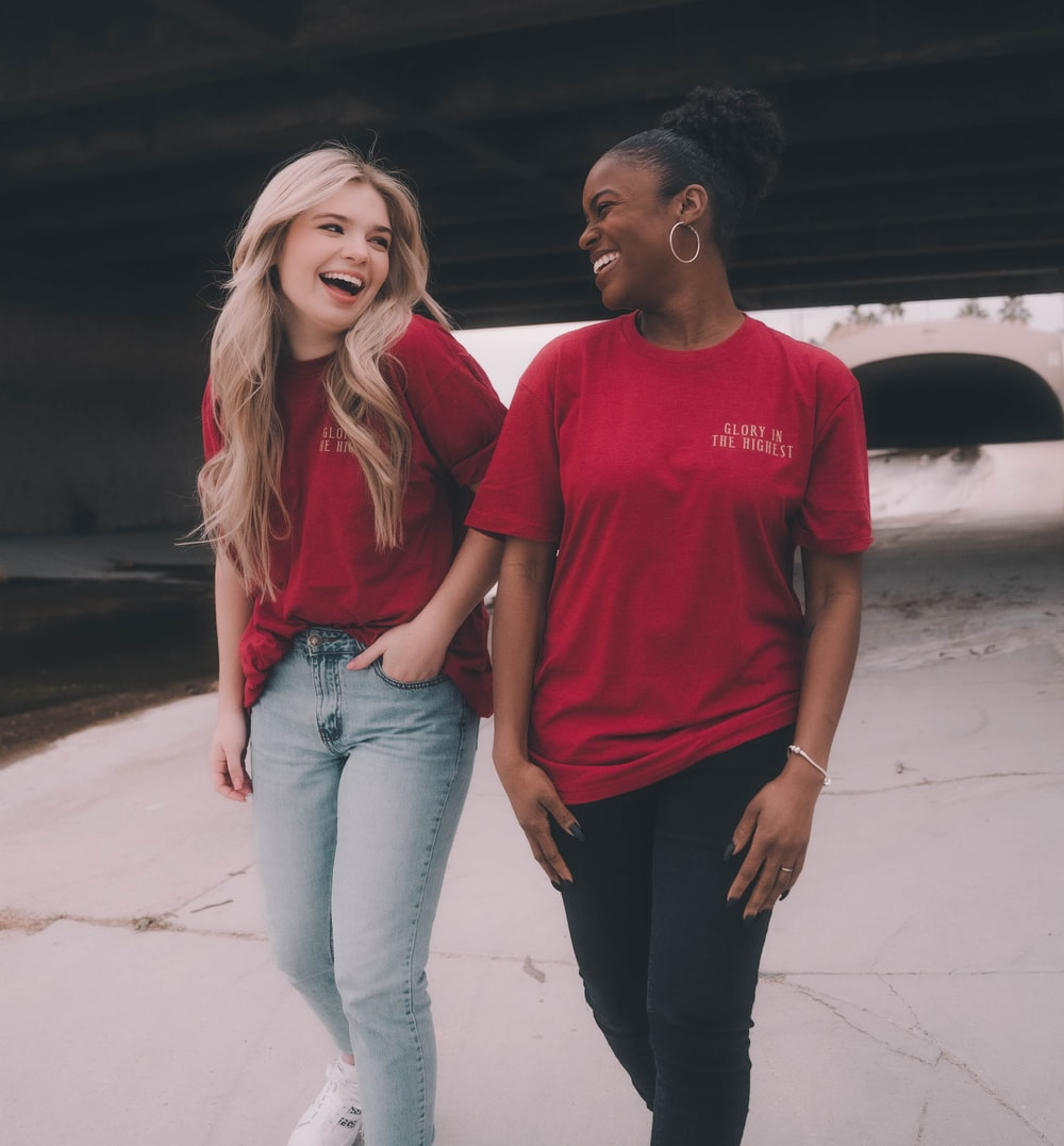 man in red crew neck t-shirt standing beside woman in red crew neck t-shirt