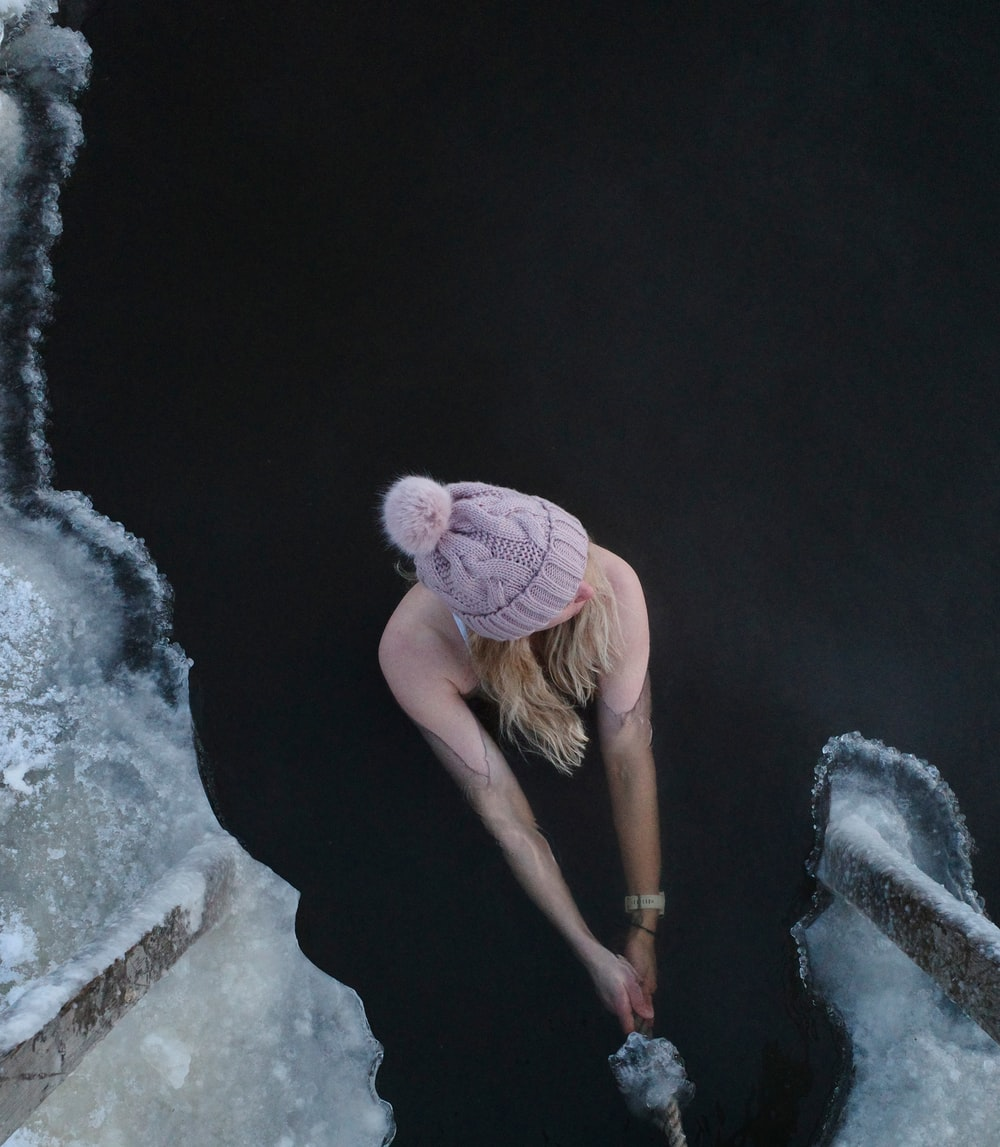 woman in pink knit cap and brown shirt climbing on rock