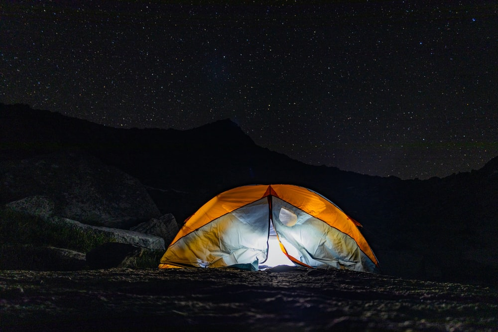 yellow tent on brown soil during night time