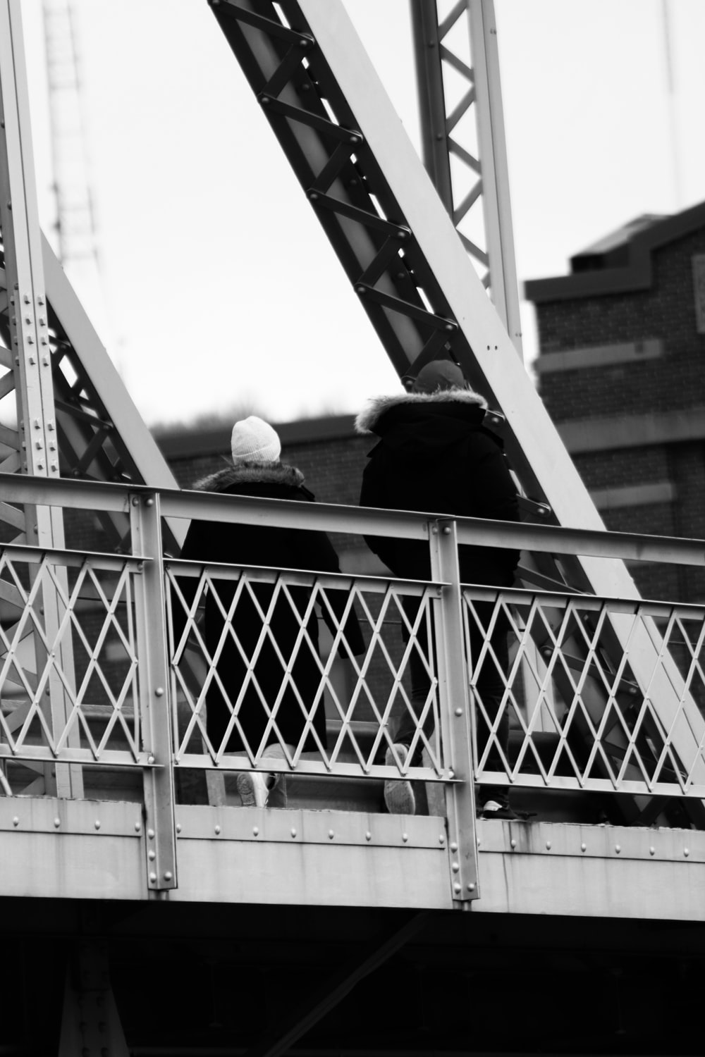 grayscale photo of man and woman kissing on the bridge