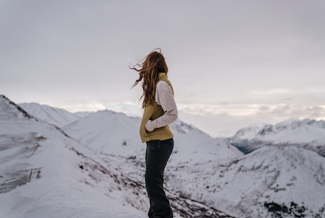 Woman In White Long Sleeve Shirt and Black Pants Standing On Snow Covered Ground During Daytime - unsplash