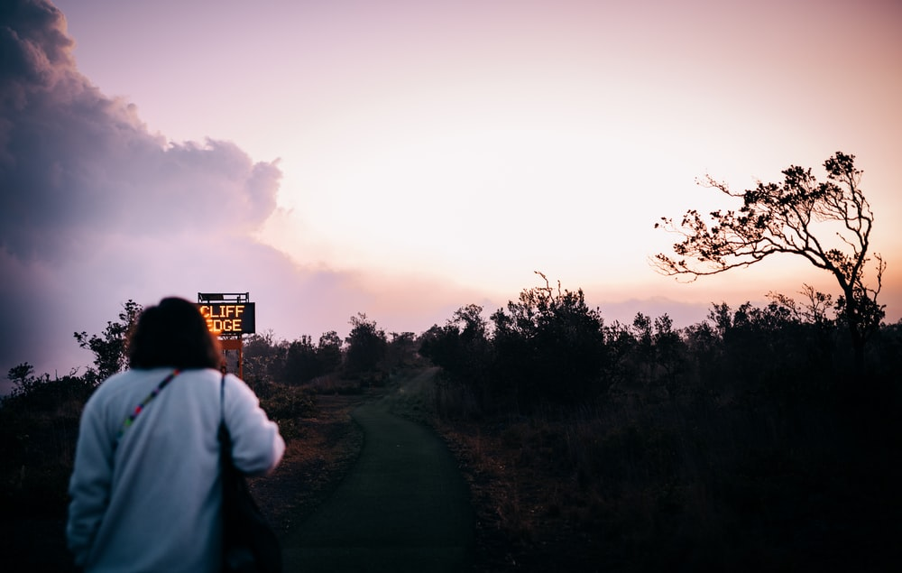 man in white shirt standing on road during sunset