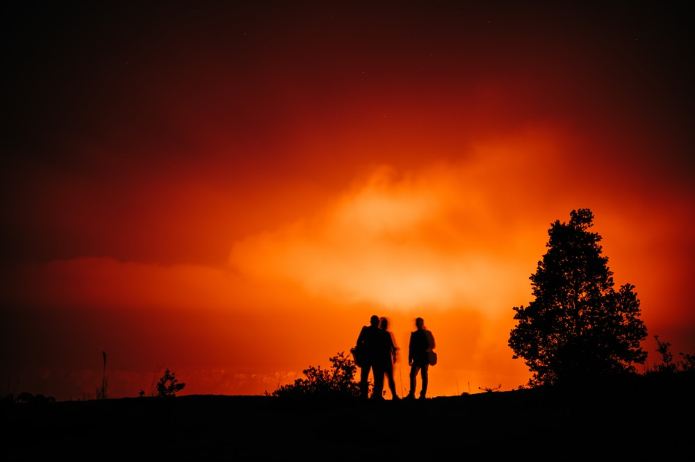 silhouette of 3 men standing on ground during sunset