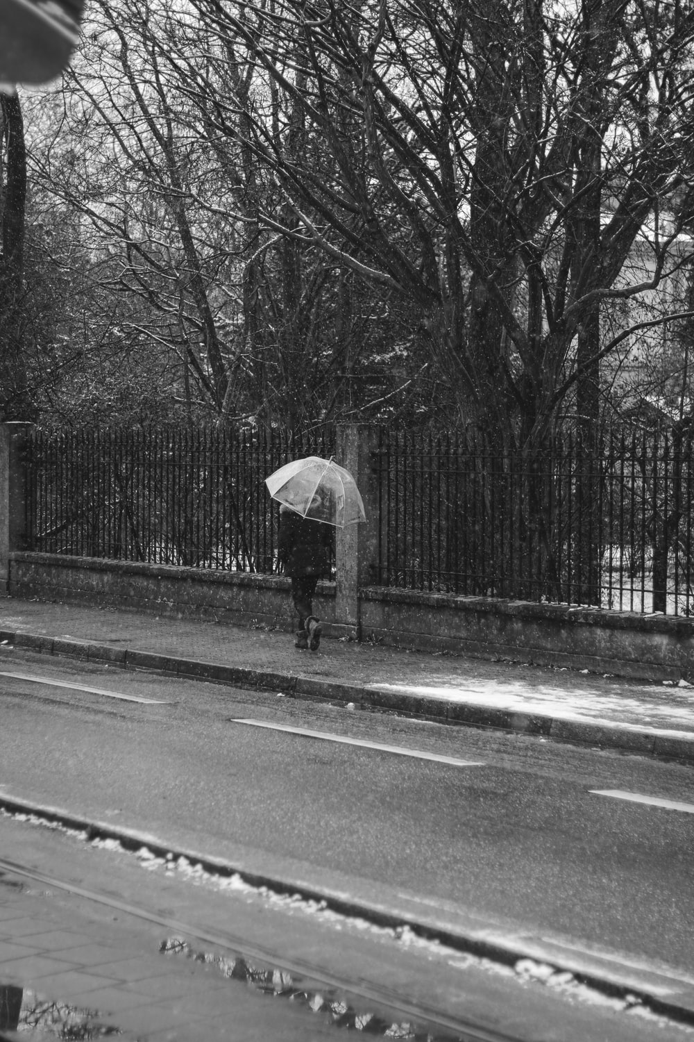 grayscale photo of person holding umbrella walking on sidewalk