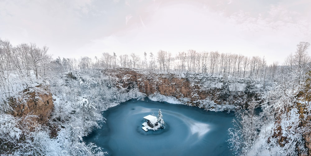 lake surrounded by snow covered trees during daytime