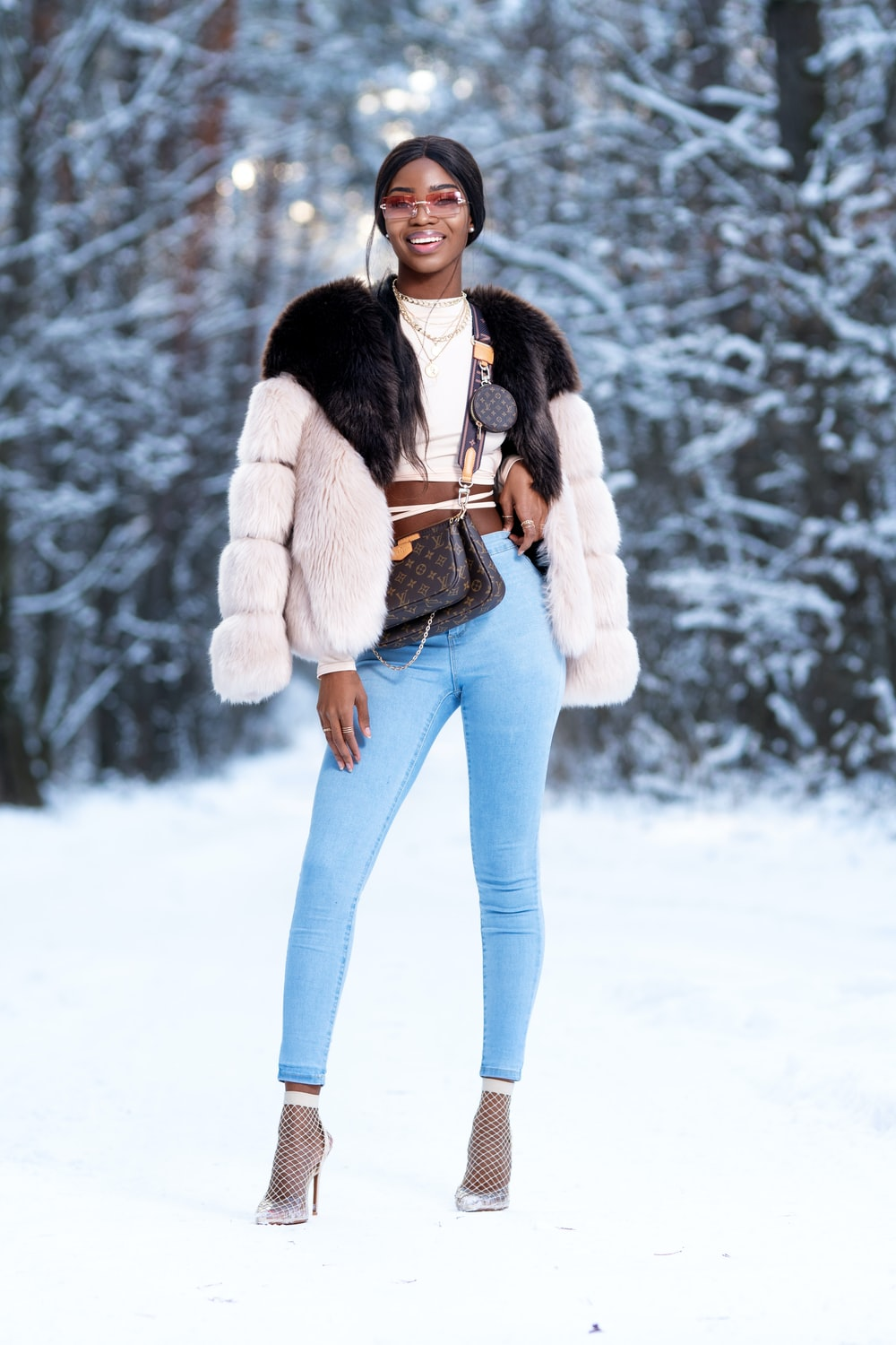 woman in white and black jacket and blue denim jeans standing on snow covered ground during