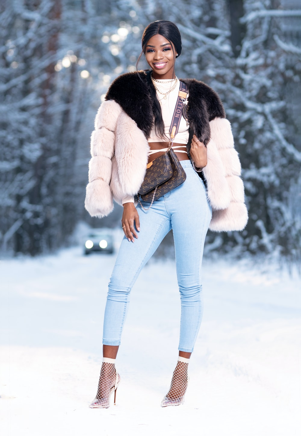 woman in white fur jacket and blue denim jeans standing on snow covered ground during daytime