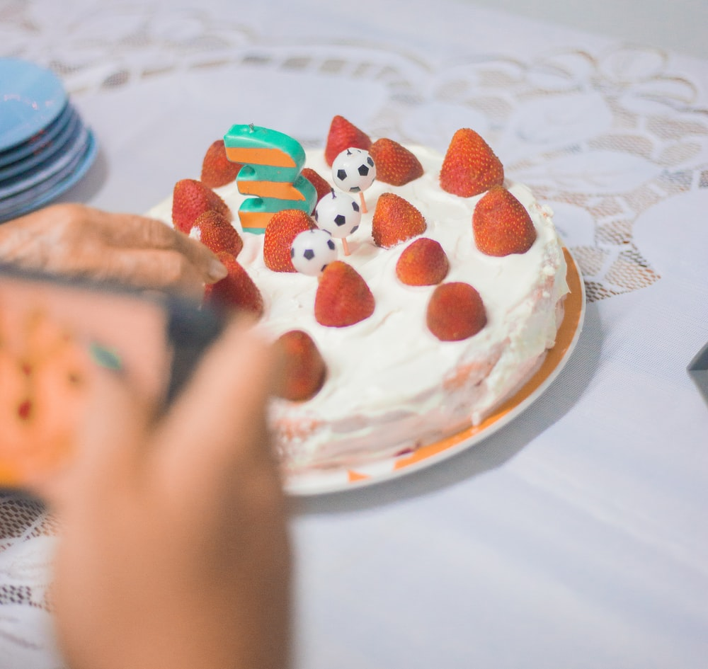person holding white and red round cake