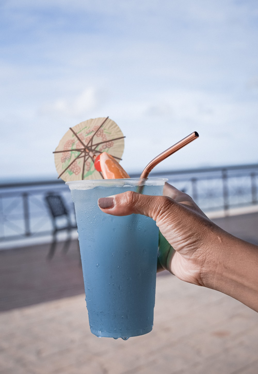 person holding blue plastic cup with brown and red umbrella
