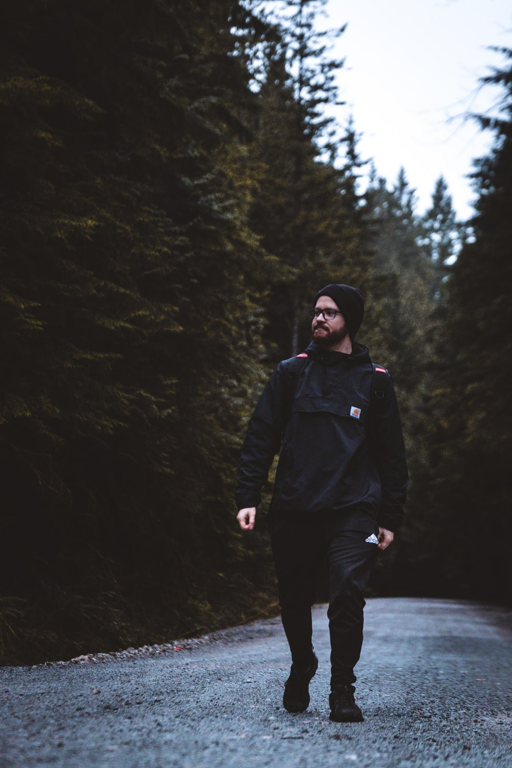 man in black jacket and black pants standing on road between trees during daytime