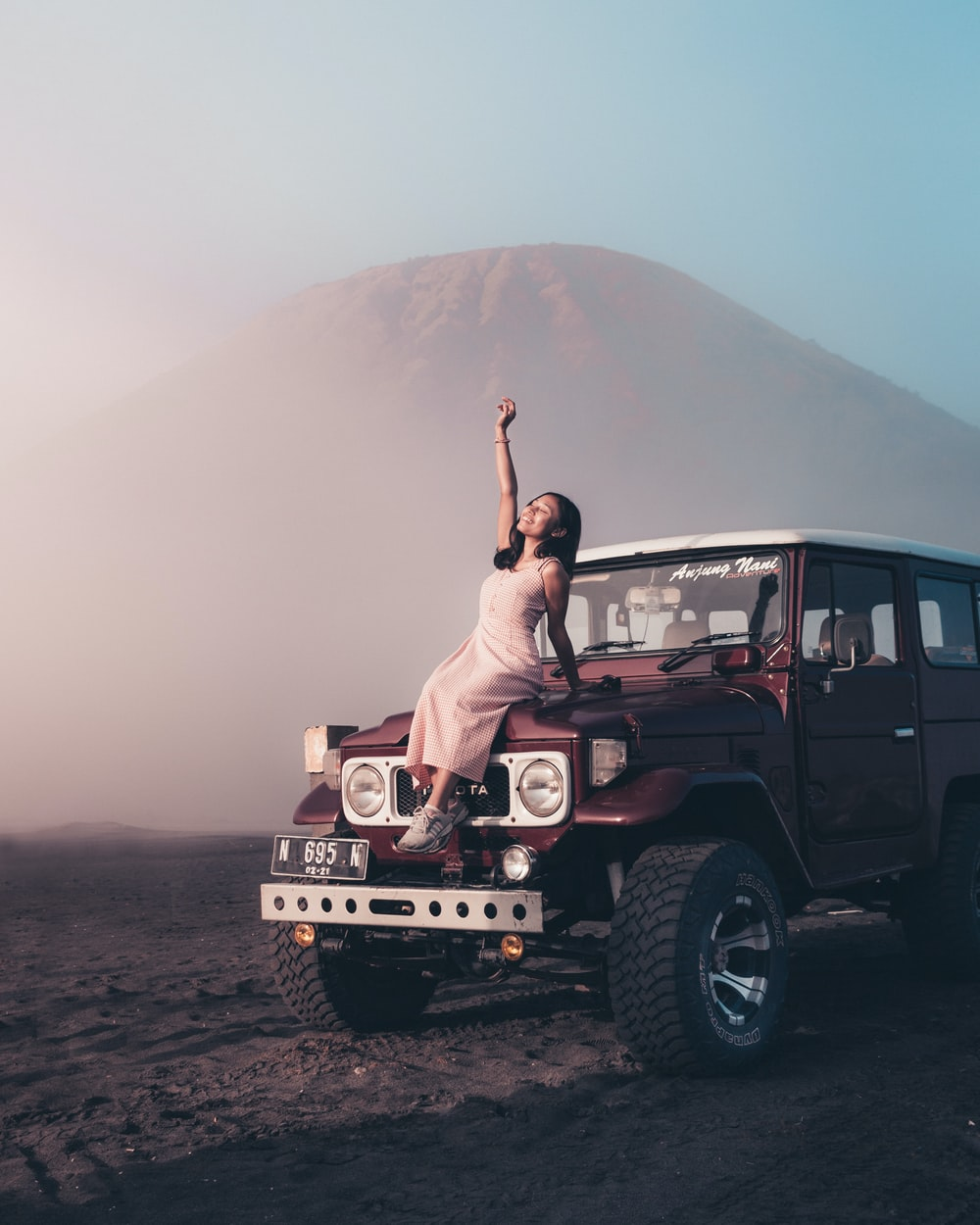 woman in white dress sitting on white jeep wrangler