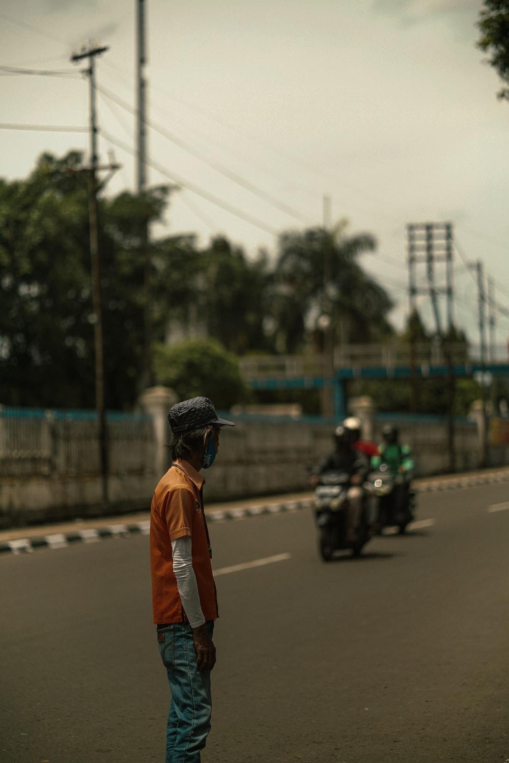 man in orange jacket and black helmet standing on road during daytime