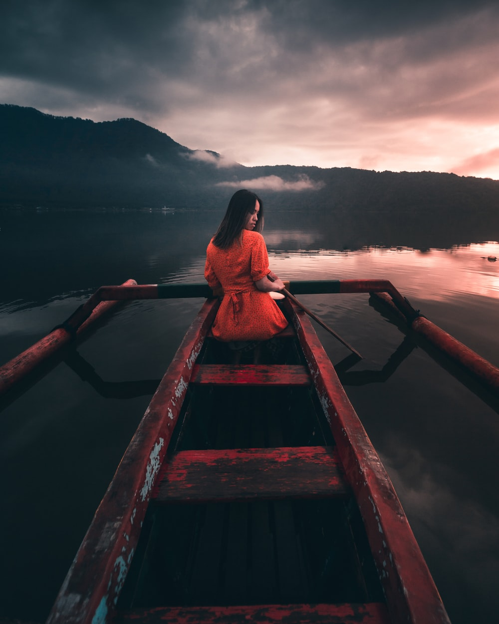 woman in red dress sitting on brown wooden dock during daytime