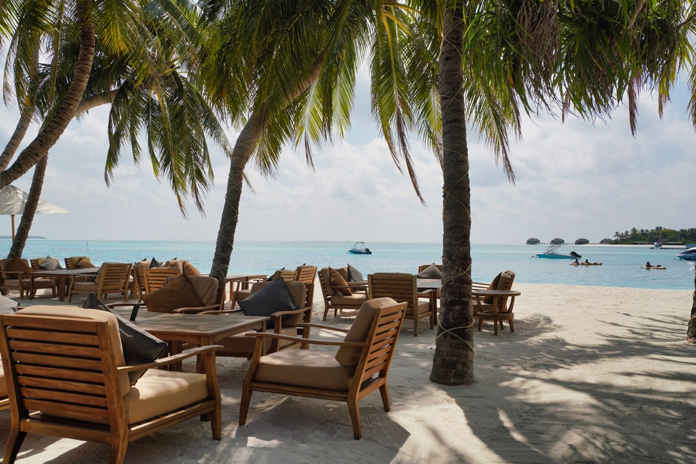 brown wooden chairs and table on beach during daytime