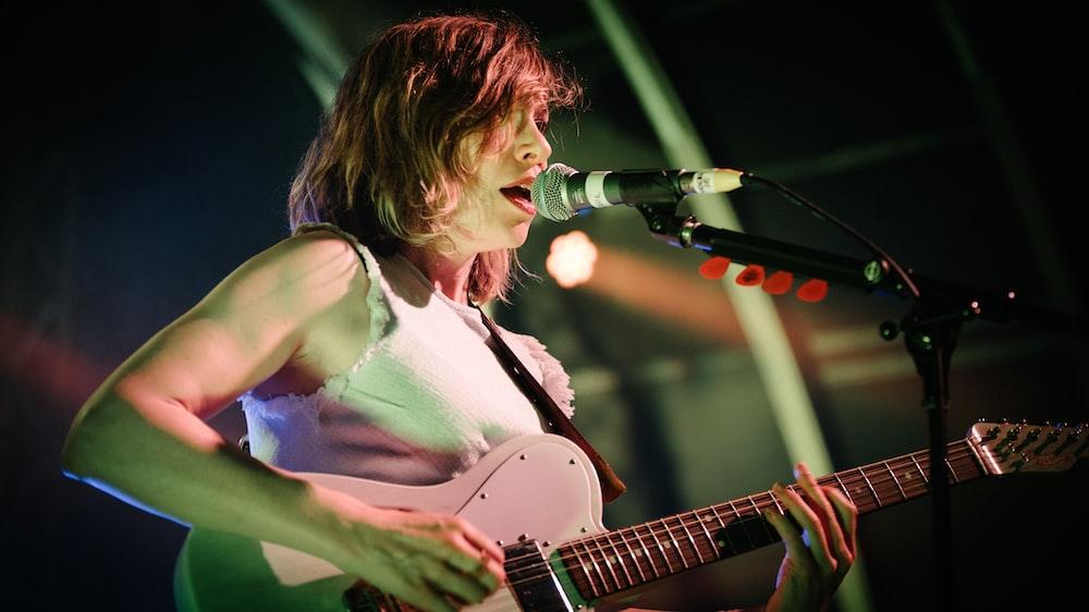 woman in white tank top playing guitar