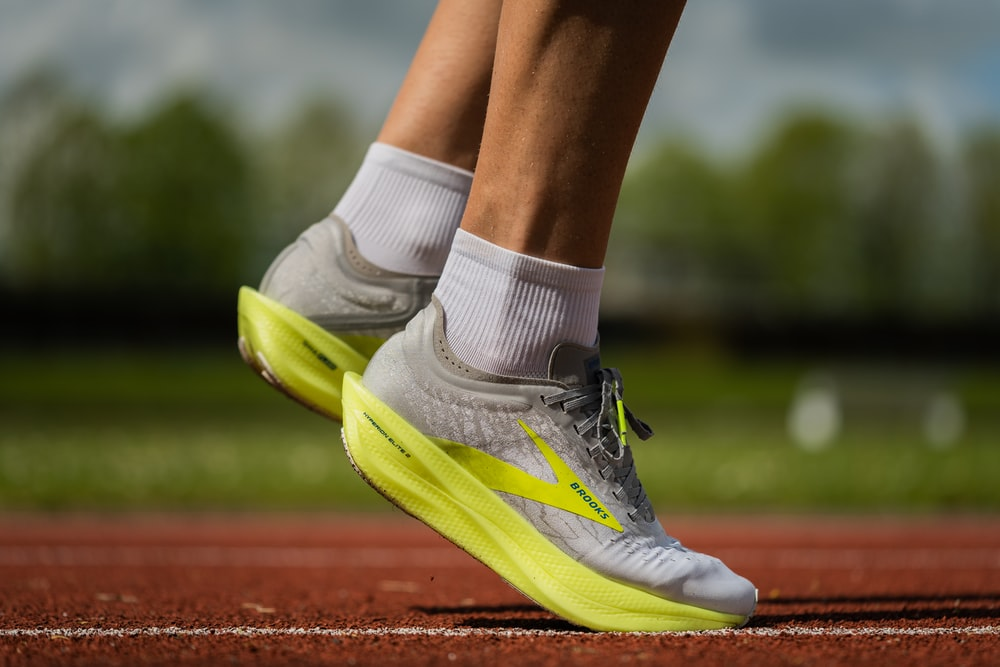 person wearing yellow and white nike athletic shoes
