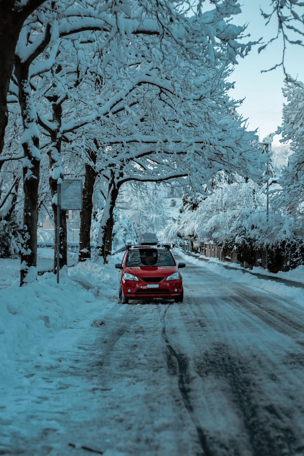 red car on road covered with snow during daytime