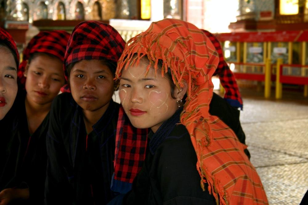 woman in black jacket beside woman in orange scarf