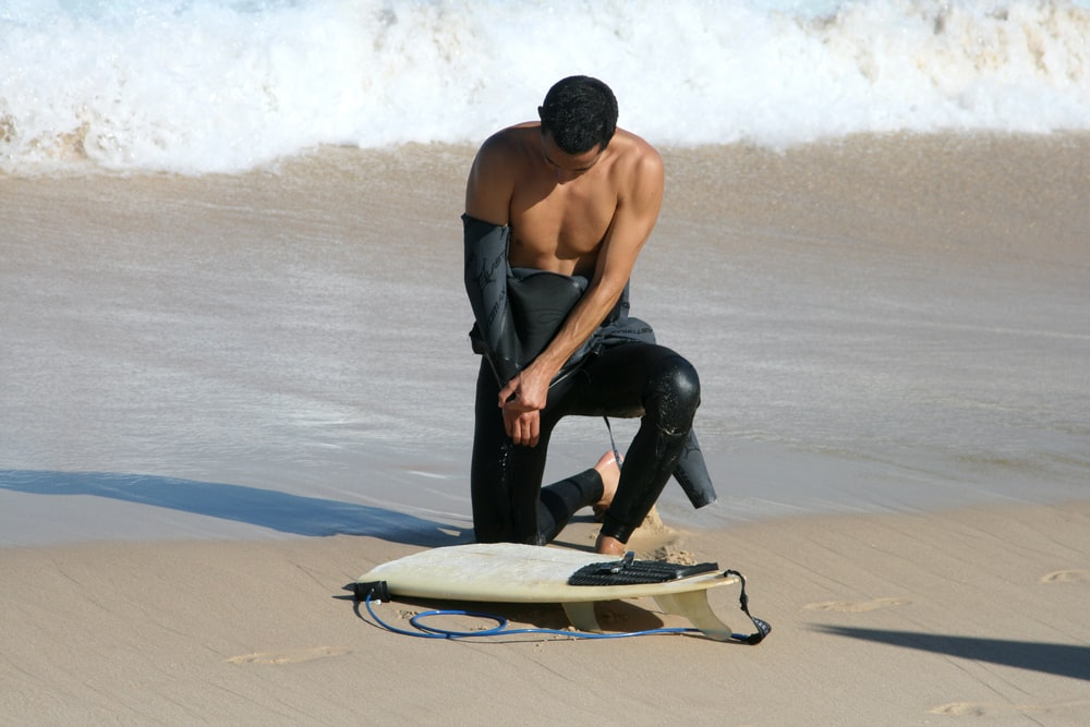 man in black pants holding white surfboard on beach during daytime