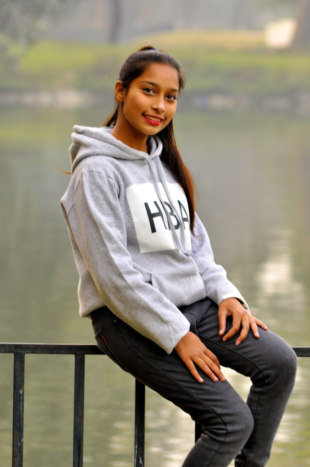 woman in gray hoodie sitting on black wooden bench