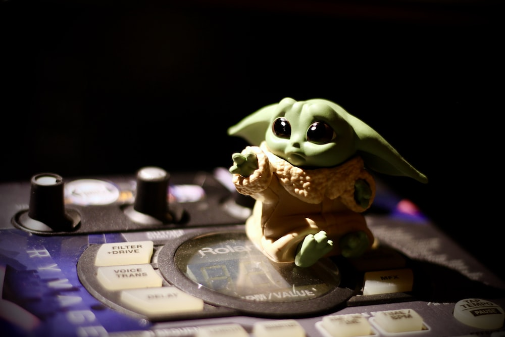 green frog figurine on black and gray dj controller